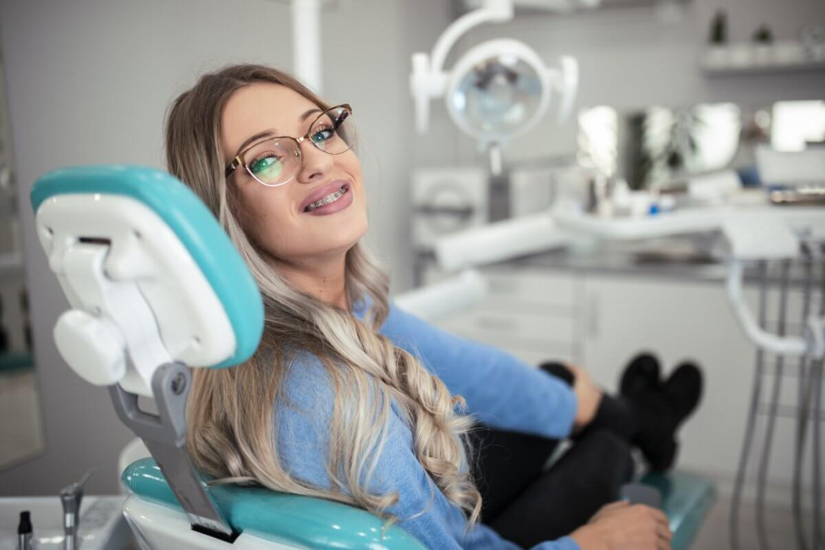 Young girl with metal braces & glasses sitting in a dentist chair and smiling.